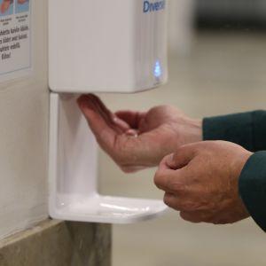 Käsi johon lasketaan käsidesiä