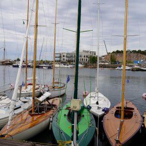 Klassiska segelbåtar i en hamn.