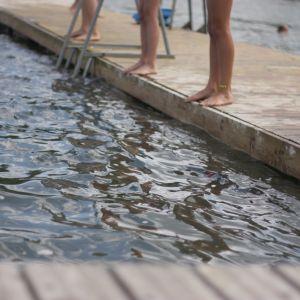 Fötter av ett antal simmare som står på en bryggkant.
