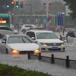 Bilar åker på översvämmad väg i Zhengzhou i Kina.