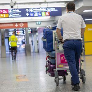 Matkalaukkukärryä työnnetään lentoasemalla.