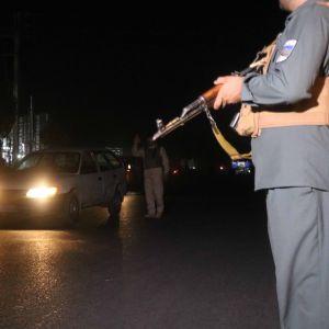 Univormupukuinen henkilö pitelee asetta, taustalla auto ajovalot päällä