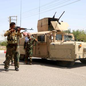 Två soldater står framför ett pansarfordon.  I bakgrunden vajar Afghanistans flagga
