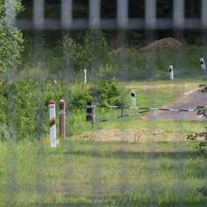 Kaksi rajapylvästä ja puomi verkkoaidan takaa kuvattuna