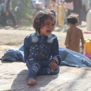 Ett gråtande barn sitter på en matta i ett dammigt flyktingläger