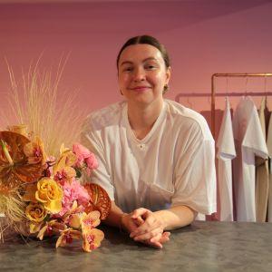 Kuvassa on helsinkiläinen kukkasuunnittelija Viivi Valkeeniemi ja hänen tekemänsä kukka-asetelma.