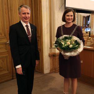 Mika Maaskola och Minna Arve står bredvid varandra i stadsfullmäktigesalen.