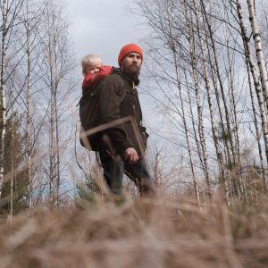 Ulkoiluvaatteisiin pukeutunut mies pieni lapsi selässään katsoo miettiväisenä kaukaisuuteen syksyisessä koivikossa