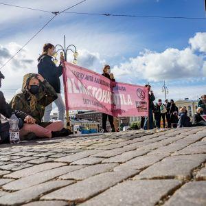 Kaksi Elokapinan mielenosoittajaa istuu kadulla, taustalla banderolli jossa lukee ilmastohätätila..