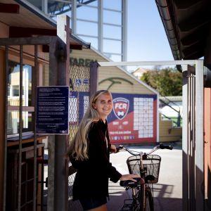 urheilija menee stadionin portista sisään ja taluttaa pyöräänsä
