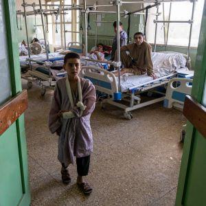 En avdelning vid ett sjukhus i Kabul där skadade i en terrorattack vårdas. En pojke med armen i bandage står i förgrunden och flera män ligger på sjukhussängar i bakgrunden.