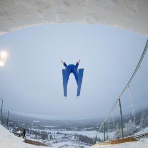 Yhdistetyn urheilija hyppää mäkeä.