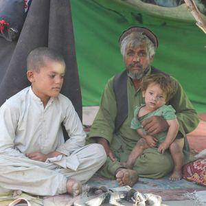 Isä pitää noen likaamaa lastaan sylissa Kabulin pakolaisleirillä.