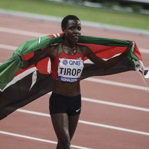 Agnes Tirop Kenian lippu harteillaan urheilusuorituksen jälkeen.