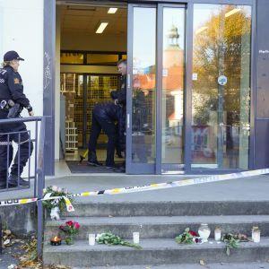 Poliisi jatkoi Kongsbergissa perjantaina kaupan tutkimista, jossa hyökkäys tapahtui. Kaupan edustalle on tuotu kukkia ja kynttilöitä.