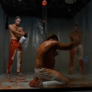 Tre personer i ett rum med inplastade väggar. De sprutar röd vätska på varandra ur sprutkannor.