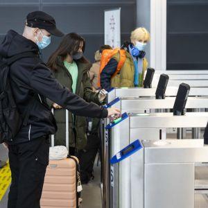 Väkeä kirjautumassa sisään terminaaliin.