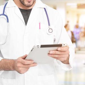 En manlig läkare som har en ipad i handen.