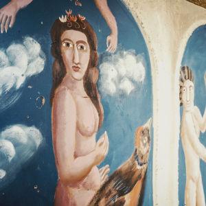 Väggmålning av nakna kvinnor och män som lutar sig mot valvbågar med blå himmel i bakgrunden.