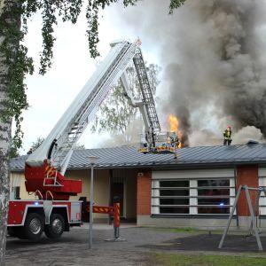 Mikkelin Tuppuralan koulu palaa, pelastaja katolla sammutustöissä.