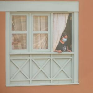 En kvinna med munskydd tittar ut från ett fönster i ett hotell.