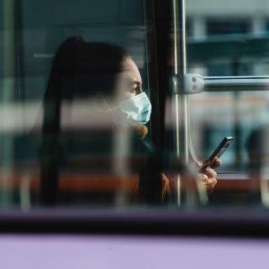 Nainen istuu raitiovaunussa hengityssuojain kasvoilla.