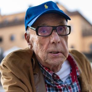 Kommerseråd Matti Koivuranta, en äldre man med glasögon och blå keps. I bakgrunden ett stort gult hus, det Rettigska palatset.