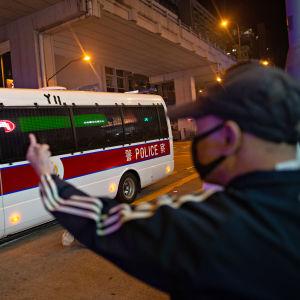 Mies reagoi käsimerkeillään ohi ajavaan poliisibussiin Hongkongissa 30. marraskuuta 2019.