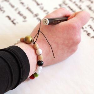 Rippikoululainen kirjoittaa paperille, rukoushelmet ranteessa.