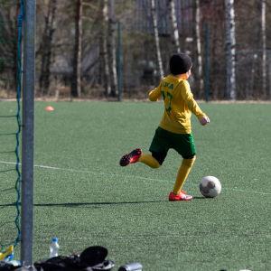 Lapset pelaavat jalkapalloa Matinkylän urheilupuistossa.