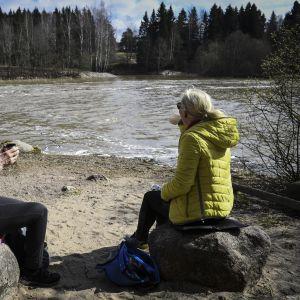 Två personer sitter ute vid en strand med koppar i handen med ryggen mot kameran.