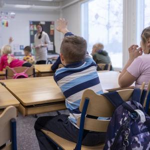 En elev sträcker upp handen och markerar under en lektion i skolan. Bredvid honom sitter en annan elev och i bakgrunden syns läraren, tavlan och fler elever.