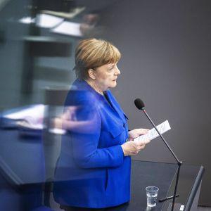 Angela Merkel puhuu Saksan liittopäiville. Hänellä on sininen takki.