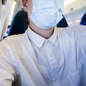 Kuvassa on matkustaja kasvomaski kasvoillaan lentokoneessa syyskuussa 2020.