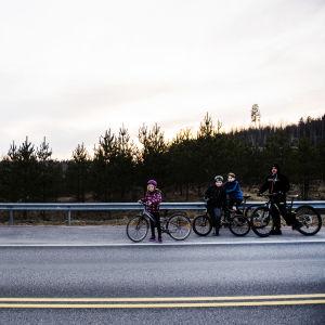 Människor med cyklar står bredvid den nyländska gränsen. Också en polisbil syns.