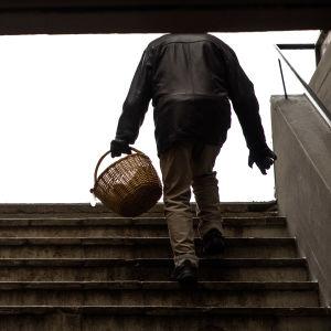 Ikääntynyt henkilö pajukori kädessä nousee portaita ostoskeskuksessa.