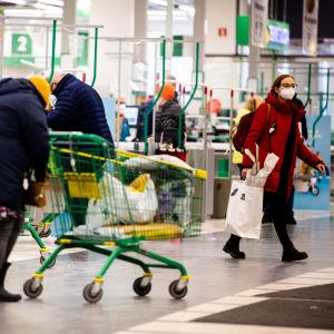 Kunder packar ihop sina varor vid rullbanden vid en mataffär.