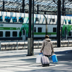 Nainen vetää matkalaukkua ja kantaa kylmälaukkuja Helsingin päärautatieasemalla 24. toukokuuta 2021.