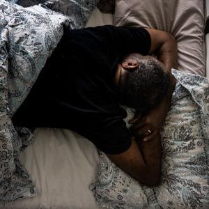 Henkilö nukkuu sängyssä.