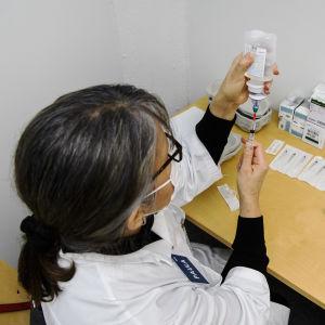 Sote-henkilöstölle annettiin Pfizerin koronavirusrokotteita Helsingissä 4. tammikuuta 2021. Sairaanhoitaja Paula valmisteli rokotteita takahuoneessa, eli sekoitti rokotetta ja keittosuolaliuosta valmiiksi ruiskuihin.