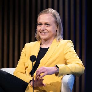 Elina lepomäki, en blond kvinna klädd i gult, sitter leende i en vit stol.