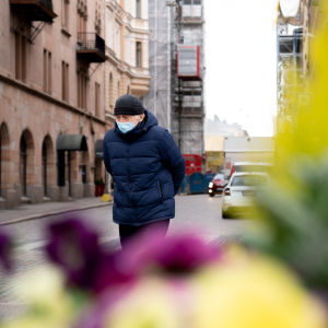 Vanha mies kävelee tien yli kasvosuojain päässä.