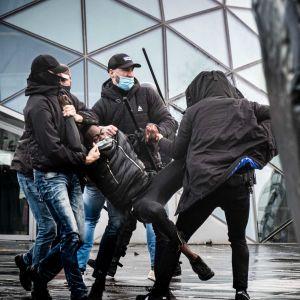 Polisen arresterar en demonstrant och bär iväg honom.