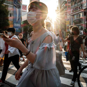 Kasvomaskeihin pukeutuneita ihmisä kadulla.
