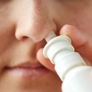 En person använder nässprej.