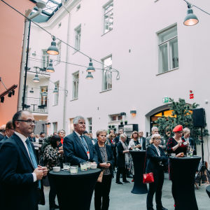 People listening to a speaker at an inner yard during a mingle.