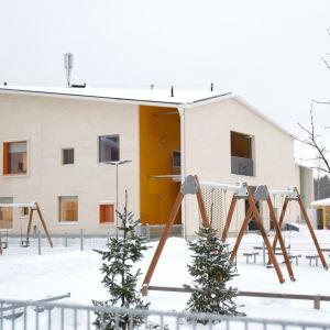 En gård med gungor. Marken är täckt av snö. I förgrunden syns en stor beige byggnad.