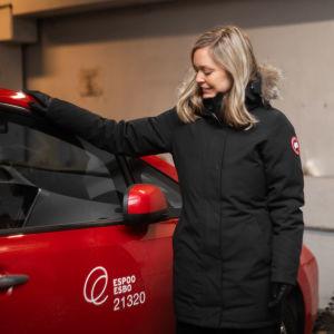 En kvinna står brevid en röd bil. Hon ser på bilen och har sin arm på dess tak. Bilen och kvinnan står i ett parkeringsgarage.