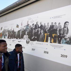 Mötesdeltagare passerar väggaffish med historisk återblick på Davos-mötena
