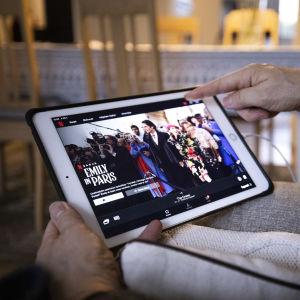 Henkilö selaa Netflixin tarjontaa iPadiltä.